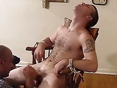 Bald man jerking tied up guys cock and enjoys it