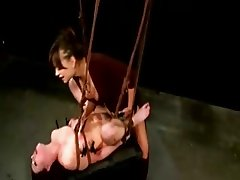 Suspended submissive gets strapon fuck