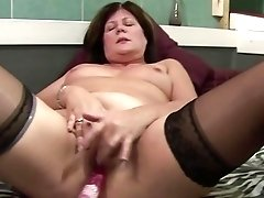 Mature retro brunette in black stockings excitingly fucks with dildo