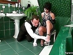 Bathroom attendant cleans up as mistress watches