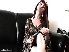 Redhead in a cute little dress smokes cigarette